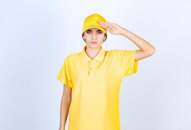 Leveringsvrouw in geel uniform staand en saluerend.