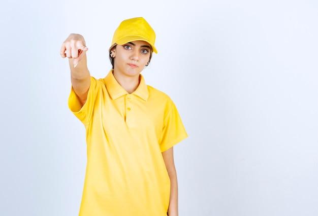 Leveringsvrouw in geel uniform staand en serieus naar de camera wijzend.