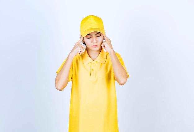 Leveringsvrouw in geel uniform staande en vingers op tempels houdend.