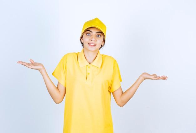 Leveringsvrouw in geel uniform staat en haalt haar armen op.