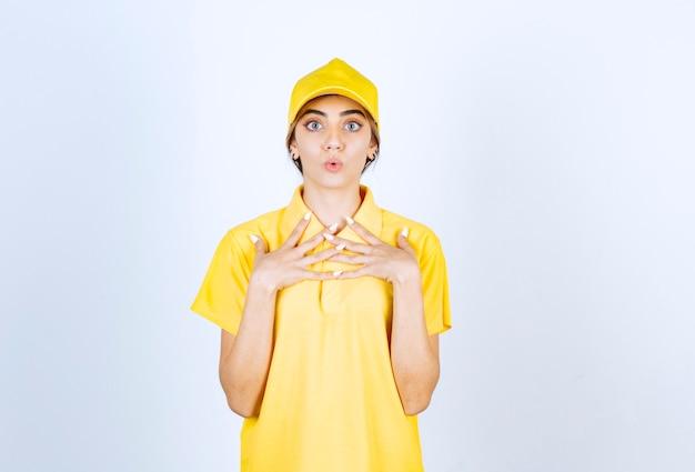 Leveringsvrouw in geel uniform staat en kijkt verrassend naar de camera.
