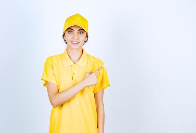Leveringsvrouw in geel uniform staat en wijst weg met een wijsvinger.