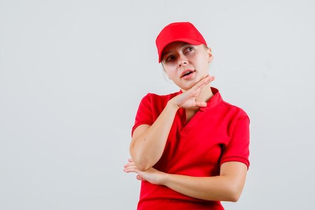 Leveringsvrouw in rood t-shirt en glb die hand op kin steunen en peinzend kijken