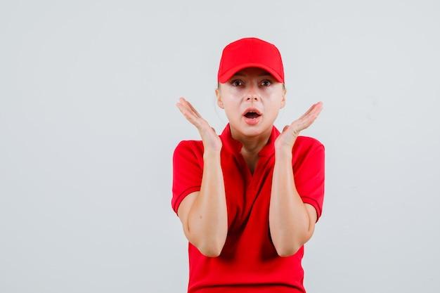Leveringsvrouw in rood t-shirt en pet die opgeheven handpalmen dichtbij gezicht houdt en verbaasd kijkt