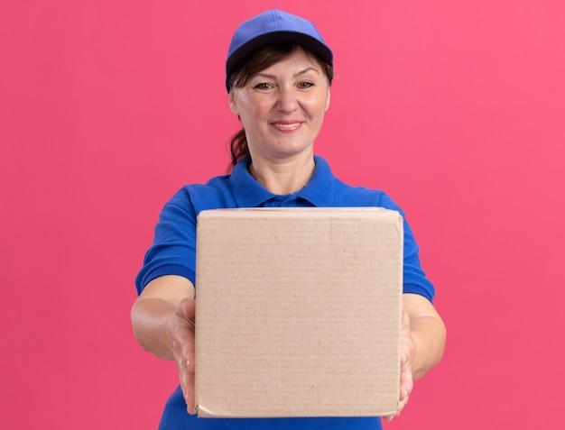 Leveringsvrouw van middelbare leeftijd in blauw uniform en glb die kartondoos tonen die voorzijde glimlachend zelfverzekerd over roze muur bekijken kijken