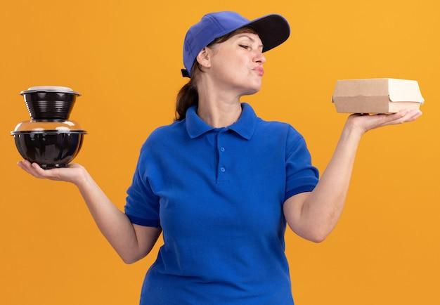 Leveringsvrouw van middelbare leeftijd in blauw uniform en pet met voedselpakketten die zelfverzekerd en gelukkig staande over oranje muur kijken