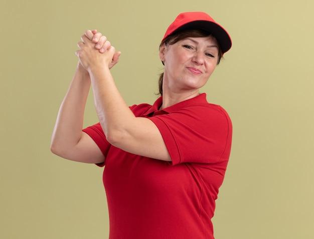Leveringsvrouw van middelbare leeftijd in rood uniform en pet die zelfverzekerde hand in hand kijken die samen groepswerkgebaar maken die zich over groene muur bevinden