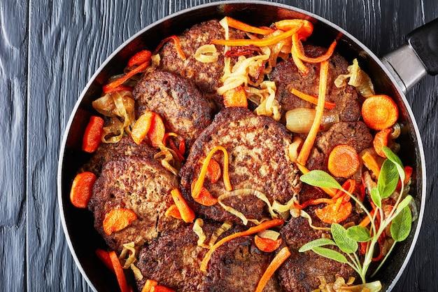 Leverpannenkoekjes gestoofd met wortel en ui in een koekenpan