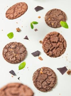 Levitatie chocolade zelfgemaakte koekjes met muntblaadjes op gele achtergrond. bovenaanzicht
