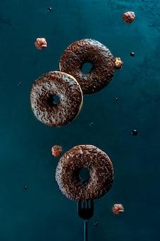Levitatie voedsel. vliegende donuts met geglazuurde chocolade
