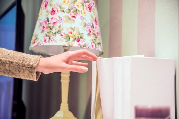 Lezen concept. vintage toon van vrouw selecteren boek uit een boekenplank. portret van serieus meisje op zoek naar een boek