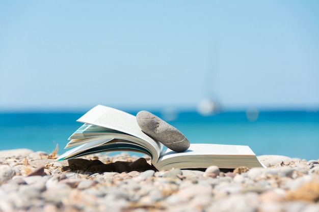 Lezen in de zomervakantie, concept. boek op het kiezelstrand.