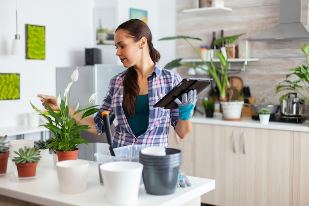 Lezen over woondecoratie op tablet-pc tijdens het controleren van planten in de keuken