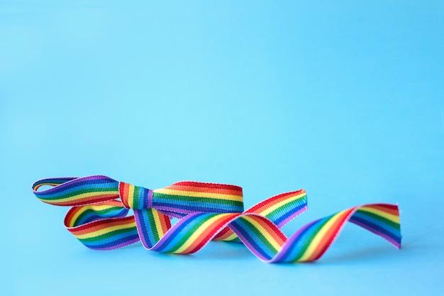 Lgbt-concept. buigen van een regenboog lint op een blauwe achtergrond