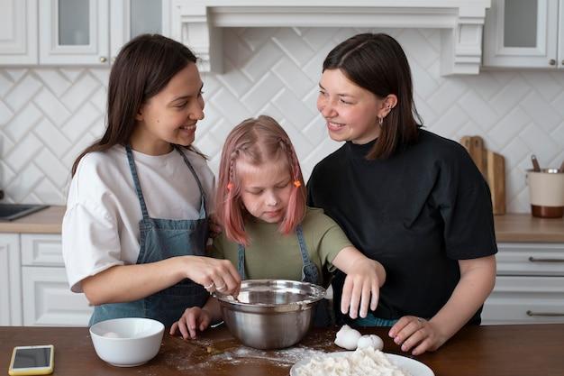 Lgbt-echtpaar brengt tijd samen met hun dochter door in de keuken