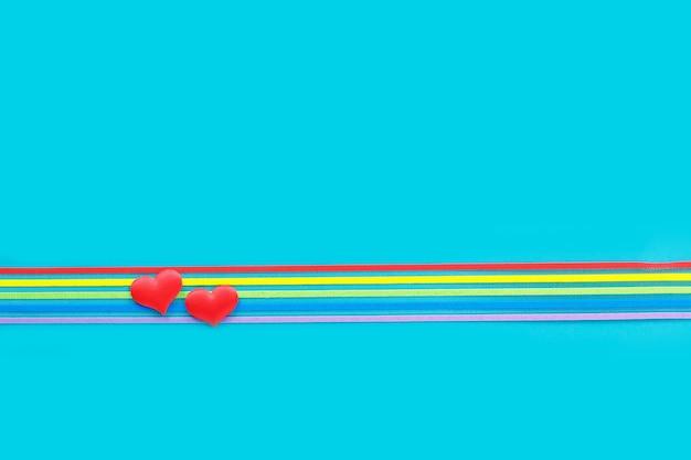 Lgbt-gemeenschap het lintvoorlichting van de trotsregenboog en twee harten op blauw