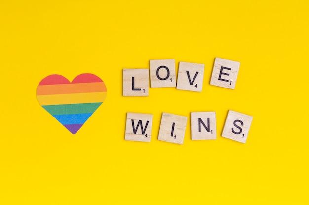 Lgbt hart pictogram en woord liefde wint op houten blokken