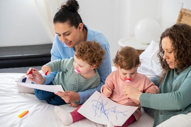 Lgbt-moeders thuis in de slaapkamer met hun kinderen