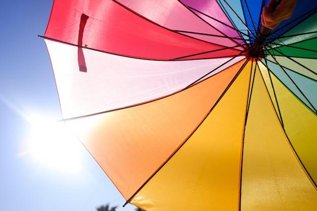 Lgbt-paraplu beschermt rechten, schijnt in de zon met vele kleuren.