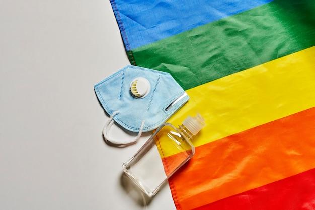 Lgbt-regenboogvlag en covid-artikelen voor persoonlijke hygiëne gezichtsmasker n gasmasker en fles desinfectiemiddel