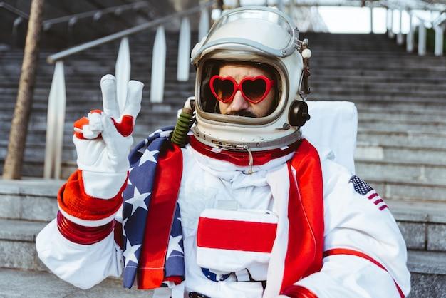 Lgbt-ruimtevaarder in een futuristisch station man met ruimtepak wandelen in een stedelijk gebied