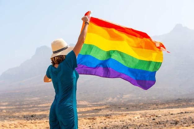 Lgbt-symbool, een lesbisch persoon in een groene jurk en een witte hoed met de regenboogvlag in de woestijn