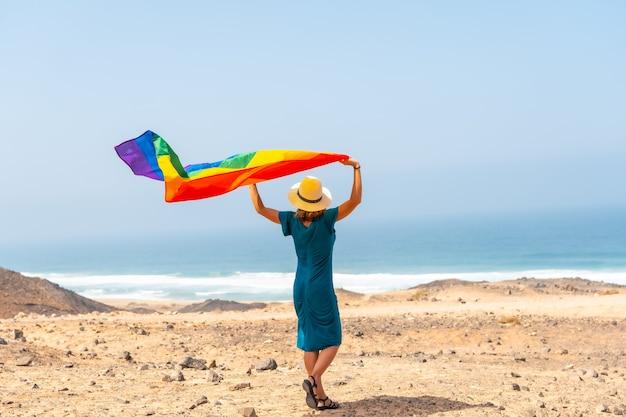 Lgbt-symbool, een lesbische persoon met een groene jurk en een witte hoed met de regenboogvlag aan zee, symbool van homoseksualiteit