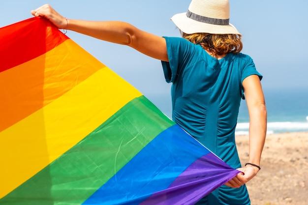 Lgbt-symbool, een onherkenbare lesbienne van achteren in een groene jurk die met de vlag zwaait bij de zee