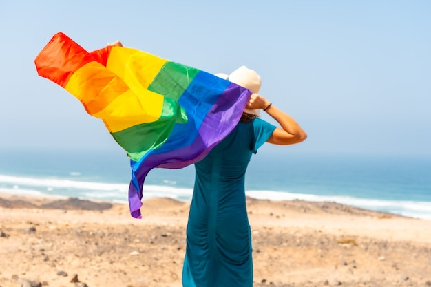 Lgbt-symbool, een onherkenbare lesbische persoon met zijn rug gedraaid in een groene jurk en een witte hoed die met de vlag zwaait bij de zee