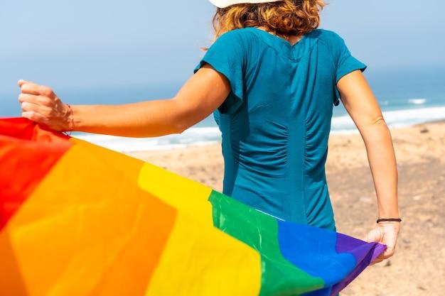 Lgbt-symbool, een onherkenbare lesbische persoon van achteren die met de vlag zwaait bij de zee