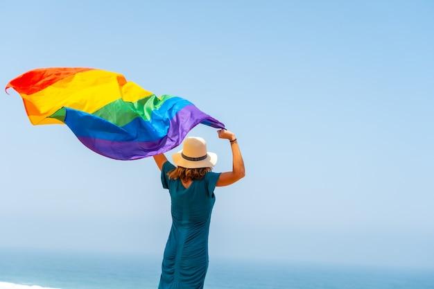 Lgbt-symbool, een onherkenbare lesbische persoon van achteren zwaaiend met de vlag en de blauwe lucht op de achtergrond