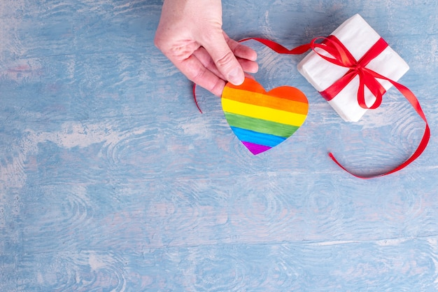 Lgbt valentijnsdag concept. valentijnsdag geschenken. hand houdt beschilderd papier lgbt-hartvorm en geschenkdoos met rood lint op blauwe houten achtergrond