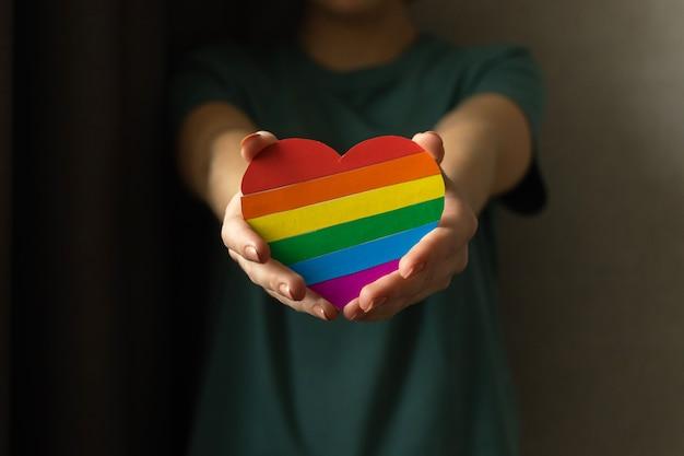 Lgbt-vlag, handen met hart in regenboogkleuren, liefdesymbool. concept van homoseksualiteit, lesbiennes en homo's, tolerantie, prijsmaand foto