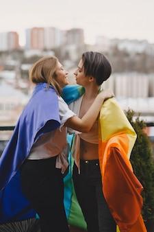 Lgbt-vlag in de buurt van meisjes. meisjes met een niet-traditionele oriëntatie. knuffels van lesbiennes.