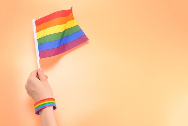 Lgbt-vlag in vrouwenhand op oranje achtergrond. ruimte kopiëren.
