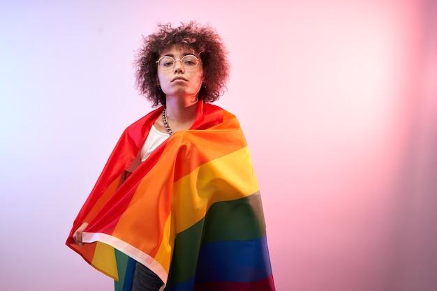 Lgbtq-concept. positief kaukasisch meisje met afro krullend haar met regenboogvlag geïsoleerd in studio in