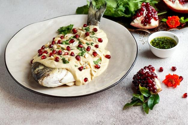 Libanese vis met tahinisaus, granaatappelpitjes en amandelen