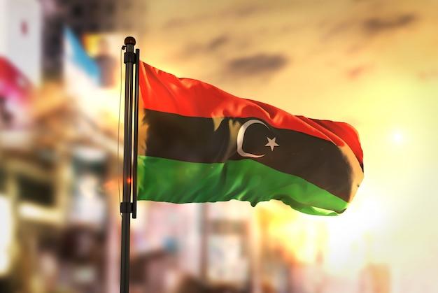 Libië vlag tegen stad wazige achtergrond bij zonsopgang achtergrondverlichting