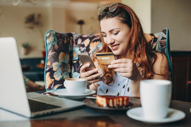 Lichaam positieve vrouw met rood haar met een creditcard en een smartphone die online transactie doet terwijl ze in een coffeeshop zit met een laptop op haar bureau.