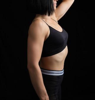 Lichaam van een meisje met atletische uitstraling in een zwarte beha en een legging