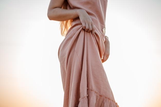 Lichaam van jonge mooie blanke blonde vrouw in roze jurk in een verlaten veld op zonsondergang