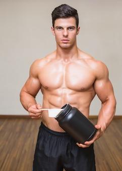 Lichaamsbouwer die een lepel van eiwitmengeling houden in gymnastiek