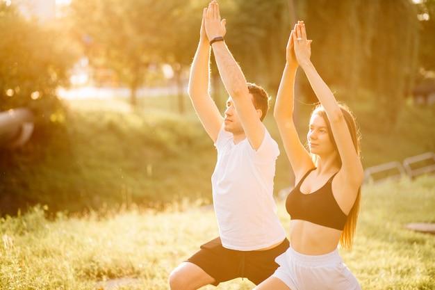 Lichaamsdeel jong koppel van man en vrouw die sporten, yoga op het stadsgazon, zomeravond, samen uitrekken op zonsondergang, stadssportstijl