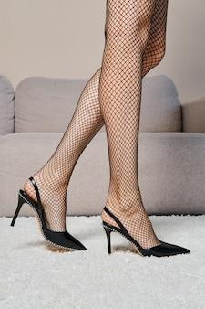 Lichaamsdelen - vrouwelijke benen in netpanty's die in profiel op het tapijt lopen