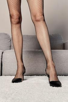 Lichaamsdelen - vrouwelijke benen in netpanty's die op het tapijt in de kamer staan