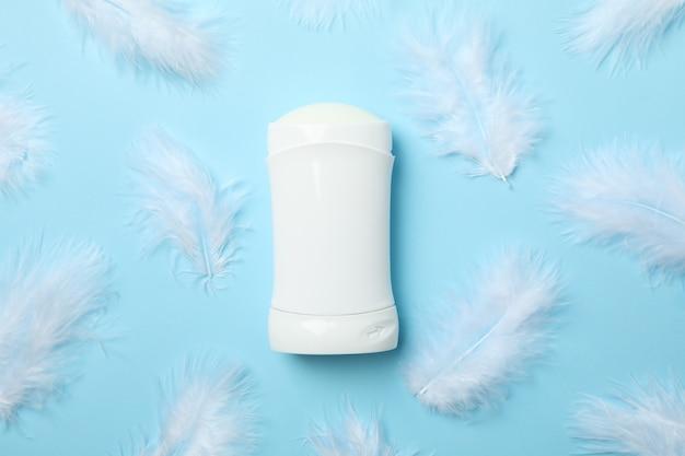 Lichaamsdeodorant en veren op blauwe achtergrond, lege ruimte voor tekst