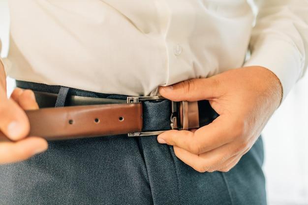 Lichaamsdetail van goedgeklede man, close-up. leren riem in vintage mode. mannen zingen riem op zijn broek vanwege maag.