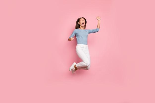 Lichaamsgrootte over de volledige lengte draaide foto van vrolijk dolblij gek opgewonden meisje dat dolblij emoties uitte springen op gezicht in broek geïsoleerde pastelkleur achtergrond