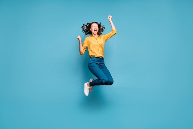 Lichaamsgrootte van de volledige lengte van mooie aantrekkelijke dromerige dolblij vrolijk vrolijk golvend meisje springen plezier goede dag.
