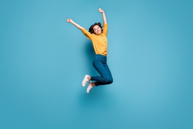 Lichaamsgrootte van de volledige lengte weergave van mooie aantrekkelijke mooie blij vrolijk golvend haar meisje springen met plezier stijgende handen omhoog.